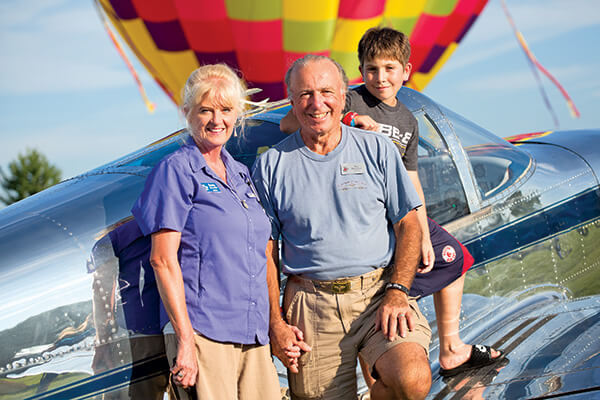 family of 3 standing in front of plane with a hot air balloon in the background